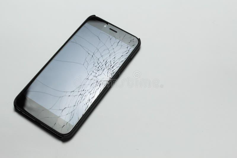Smartphone móvel com a tela quebrada no fundo branco fotos de stock