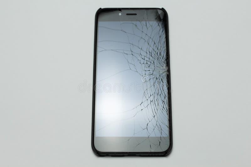 Smartphone móvil con la pantalla quebrada en el fondo blanco imagen de archivo
