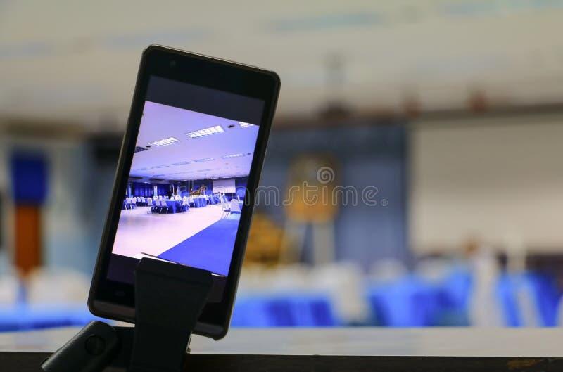 Smartphone machen ein Foto auf Schirm des ausgewählten Fokus des Konferenzzimmer-Geschäfts mit flacher Schärfentiefe lizenzfreies stockfoto