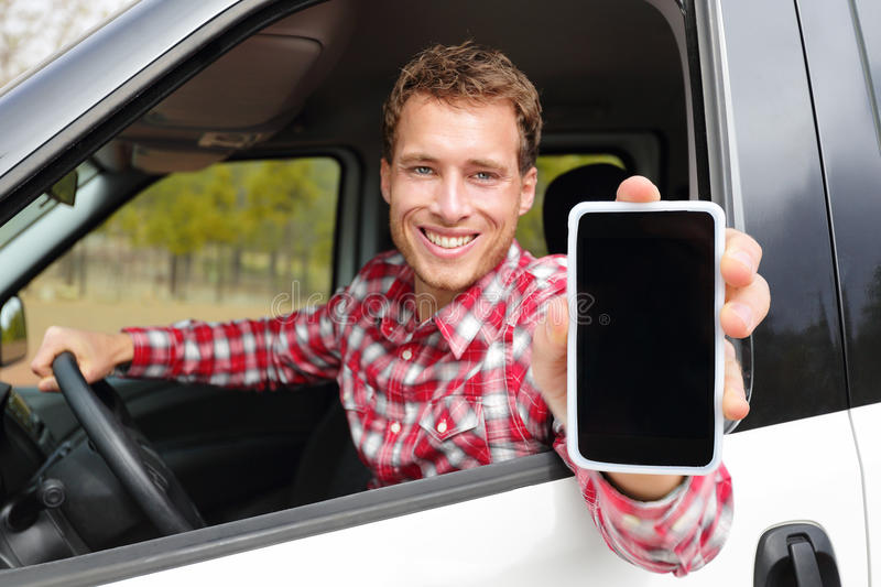 Smartphone man driving car showing app on screen. Display smiling happy. Male driver using 4g apps showing blank empty touchscreen sitting in drivers seat