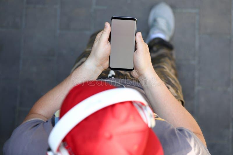 Smartphone masculino da posse da mão com placa fotos de stock royalty free