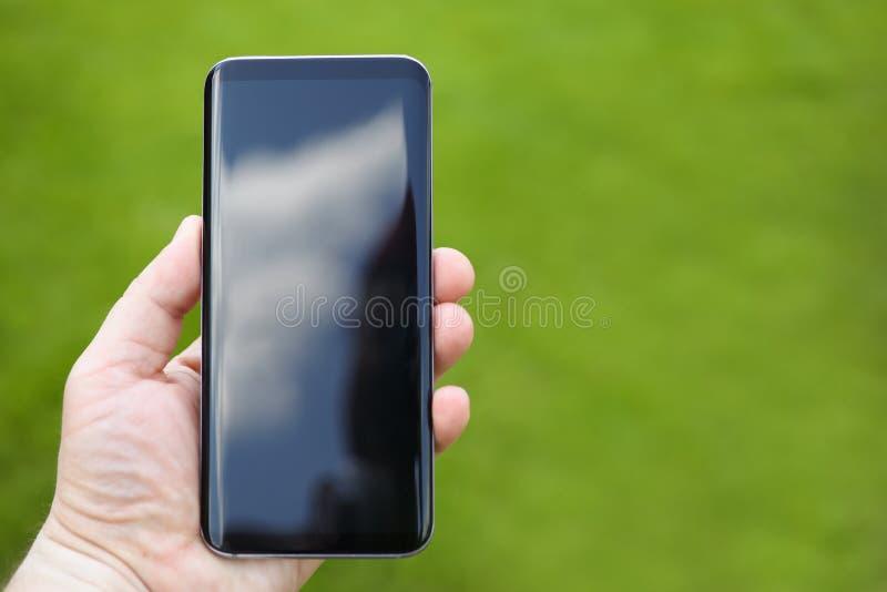 Smartphone masculino da posse da mão contra o verde imagem de stock