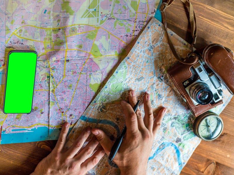 Smartphone masculino del presionado a mano La compra marca en línea y viaje de planificación junto con el mapa, pasaporte, esenci imágenes de archivo libres de regalías