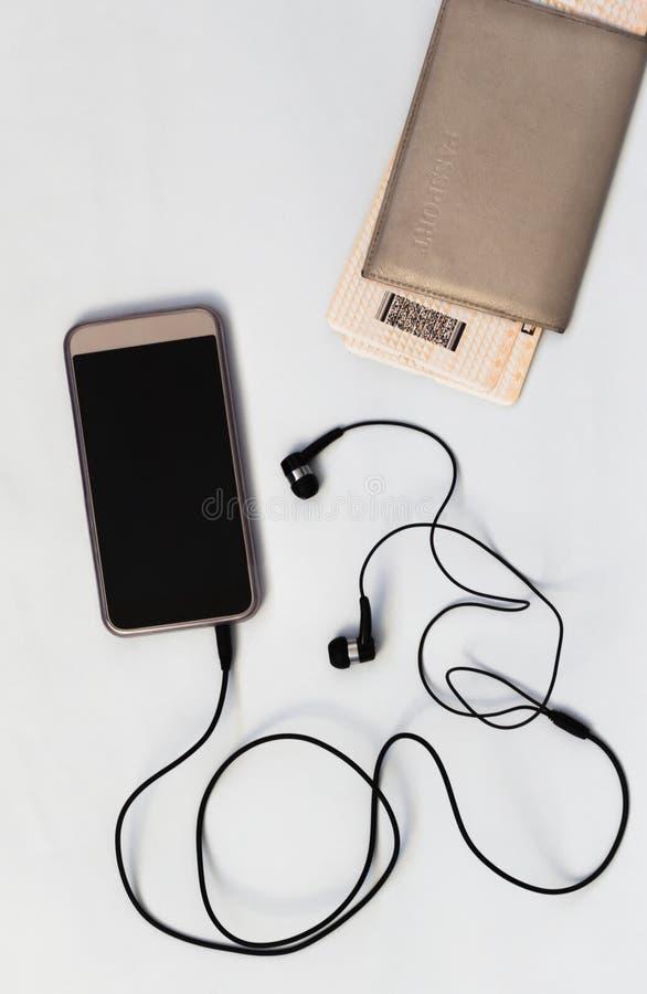 Smartphone med den tomma skärmen med hörlurar och passet, loppbegrepp med musik, bästa sikt för vit bakgrund royaltyfria foton