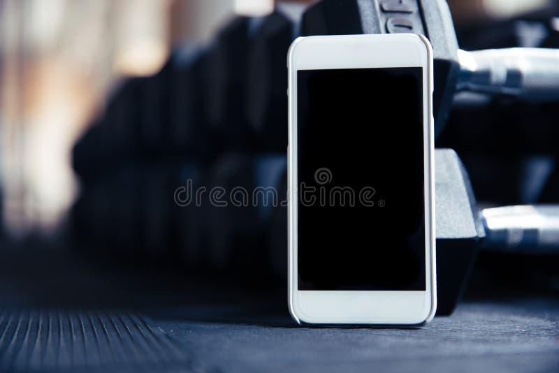 Smartphone med den tomma skärmen i idrottshall arkivfoto