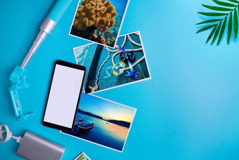 Smartphone med den tomma sk?rmen, reklamblad, foto p? bl? bakgrund ?tl?je upp, framl?nges lekmanna- sommar f?r sn?ckskal f?r sand royaltyfria foton