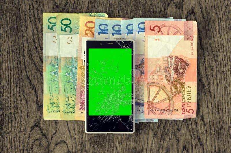 Smartphone med pengarsedlar på trätabellen royaltyfria foton