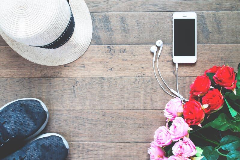 Smartphone med röda och rosa rosor, hatten och gymnastikskon på det wood golvet royaltyfri bild