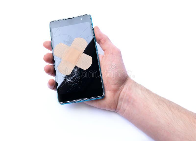 Smartphone med sprucken skärm i hand och bindemedel förbinder begrepp av reparationstelefoner royaltyfri fotografi