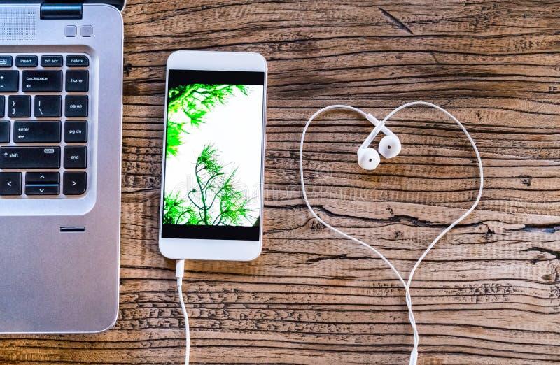 Smartphone met de witte oortelefoon van de hartvorm en computerlaptop op werkende lijstvlakte leggen samenstellings hoogste menin royalty-vrije stock afbeelding