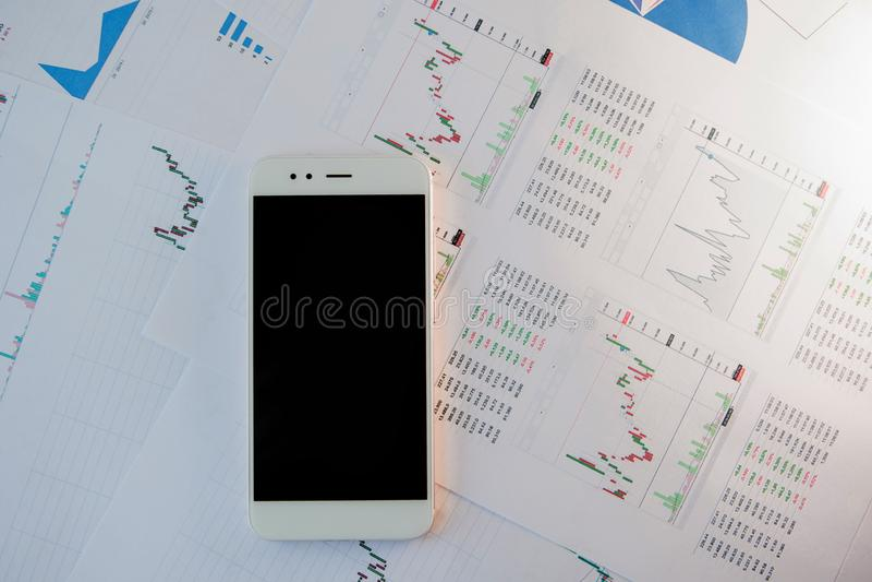 Smartphone met het lege scherm op achtergrond van financiële verslagen royalty-vrije stock afbeeldingen