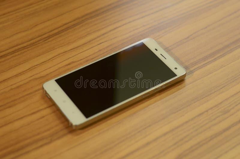 Smartphone met het lege scherm op houten lijst stock afbeeldingen