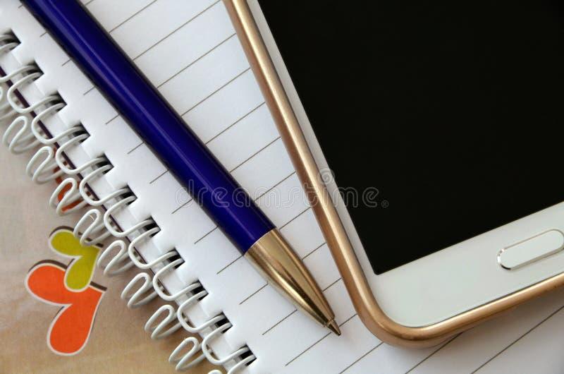 Smartphone met notitieboekje, pen en harten stock afbeeldingen