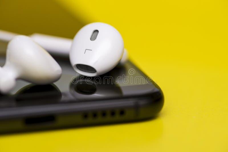 Smartphone met oortelefoons op kleurenachtergrond Smartphone en oortelefoon op gele achtergrond Close-up van smartphone met royalty-vrije stock afbeeldingen