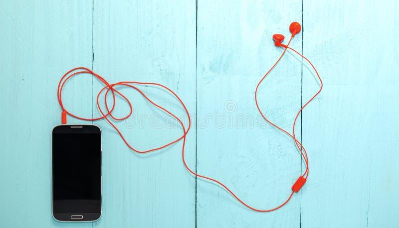 Smartphone met rode oortelefoon op blauwe houten achtergrond royalty-vrije stock afbeeldingen