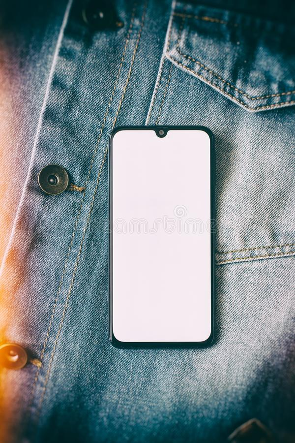 Smartphone mit Anzeige auf dem ganzen Bildschirm auf dem Jeanshintergrund stockbilder