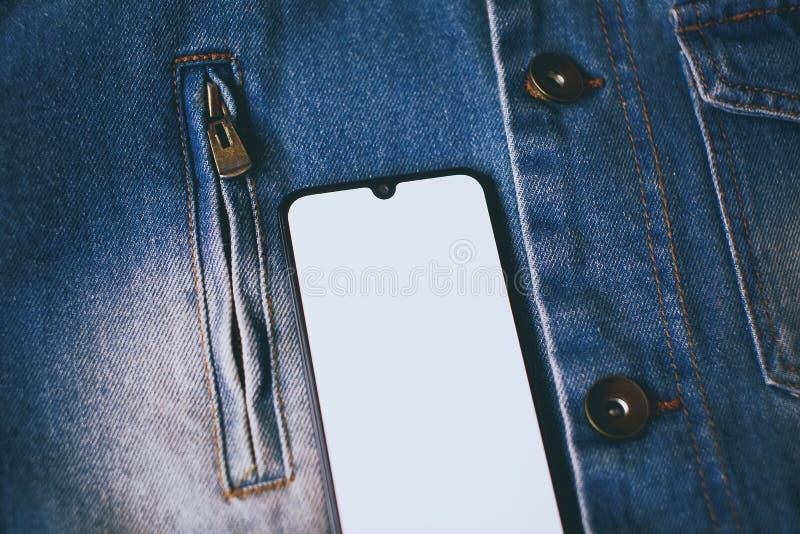 Smartphone mit Anzeige auf dem ganzen Bildschirm auf dem Jeanshintergrund lizenzfreies stockfoto