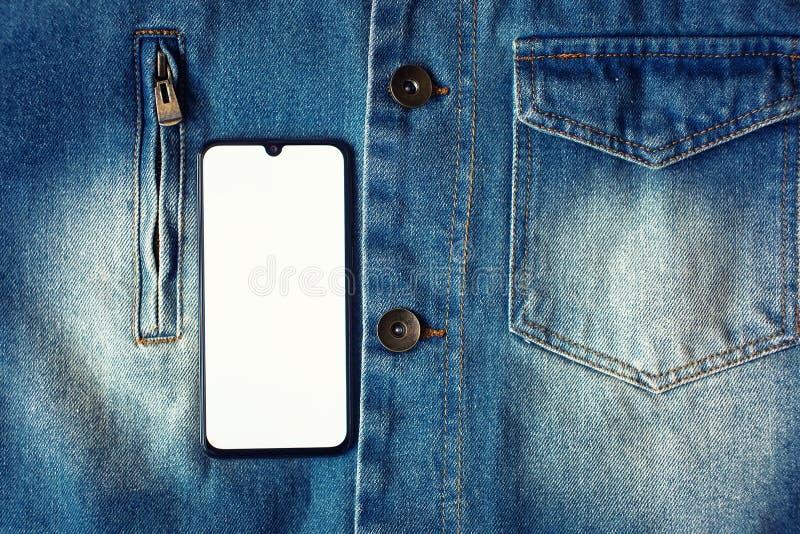 Smartphone mit Anzeige auf dem ganzen Bildschirm auf dem Jeanshintergrund stockfotografie