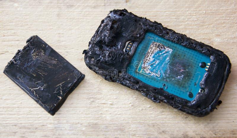 Smartphone mit Batterieproblem, Handybatteriebrand wegen der Hitze auf hölzernem Hintergrund lizenzfreie stockfotografie