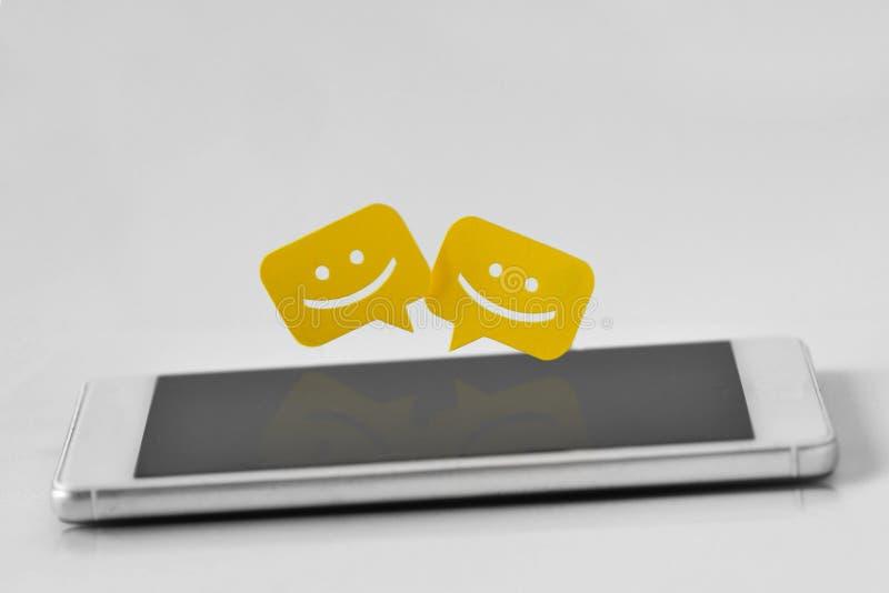 Smartphone mit Schwätzchenmitteilungsblasen auf weißem Hintergrund stockfotografie
