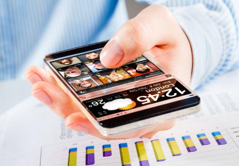 Smartphone mit transparentem Schirm in den menschlichen Händen stockbild