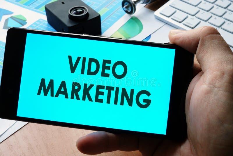 Smartphone mit Zeichenvideomarketing-Konzept stockfotografie