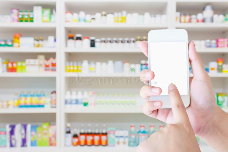 Smartphone mobile della tenuta femminile del farmacista nella farmacia fotografia stock