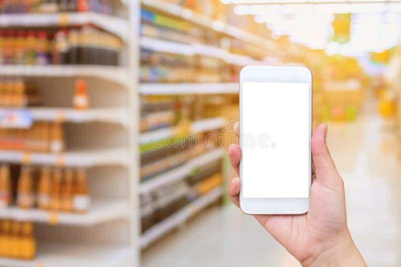 Smartphone mobile della tenuta femminile della mano sopra il supermercato immagine stock