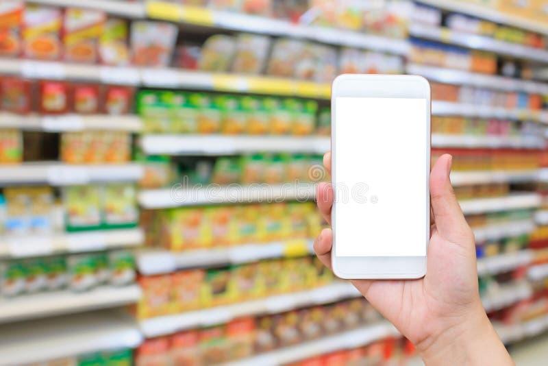 Smartphone mobile della tenuta femminile della mano sopra il supermercato fotografie stock libere da diritti