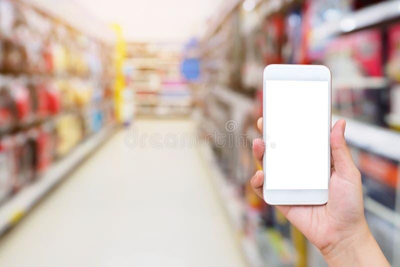 Smartphone mobile della tenuta femminile della mano sulla navata laterale del supermercato immagini stock libere da diritti
