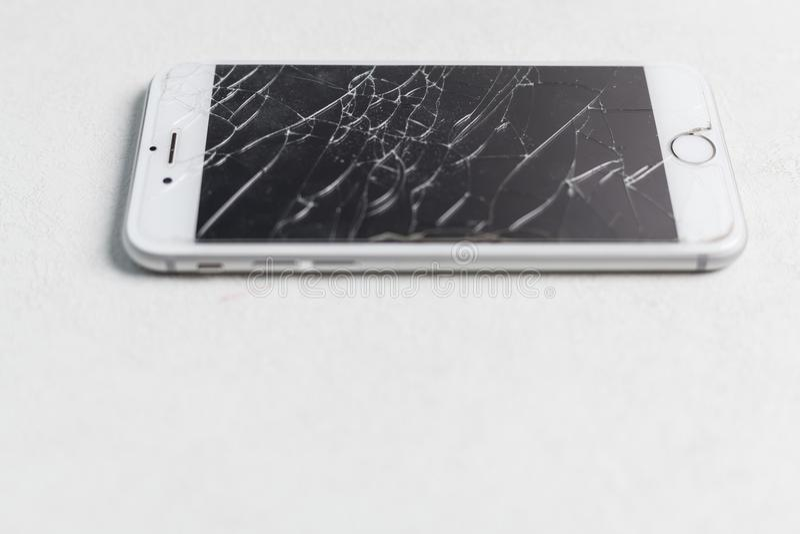 Smartphone mobile moderne avec l'écran cassé sur le fond blanc photographie stock libre de droits