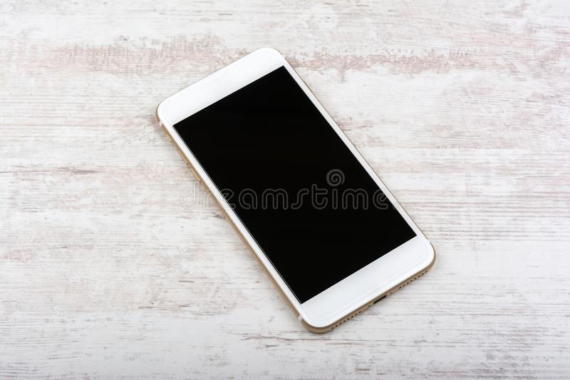 Smartphone mock-up with blank black screen. Front view of a cellphone on white wooden background royalty free stock images