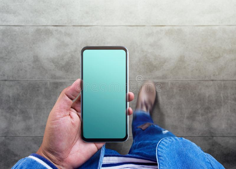 Smartphone Mockup image, Top View of Male Walking on the Street. While using Mobile Phone. Screen is Blank Clipping Path stock images