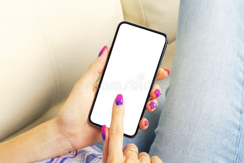 Smartphone modell i kvinnahand Ny modern svart frameless smartphone?tl?je upp med den tomma vita sk?rmen Tomt avst?nd f?r text ko arkivfoto