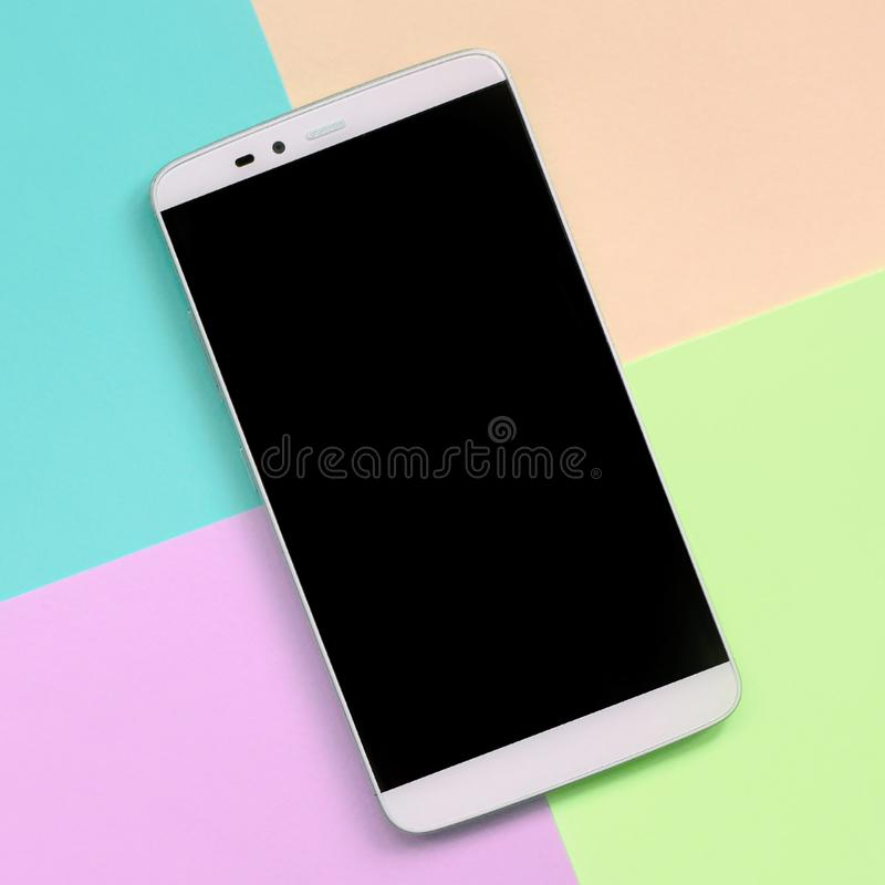 Smartphone moderne avec l'écran noir sur le fond de texture de couleurs en pastel roses de mode, bleues, de corail et de chaux photo stock