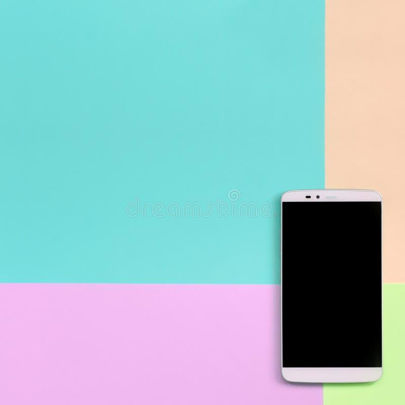 Smartphone moderne avec l'écran noir sur le fond de texture de couleurs en pastel roses de mode, bleues, de corail et de chaux images libres de droits