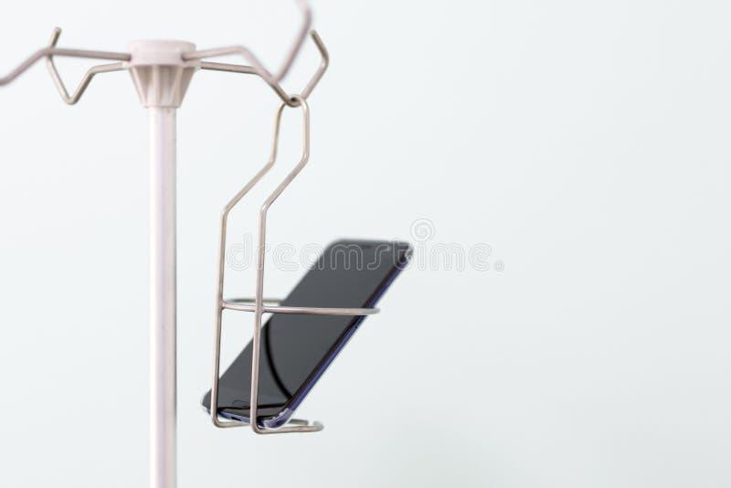 Smartphone moderne noir dans un support médical de compte-gouttes Téléphone et concept social de dépendance de réseau image libre de droits