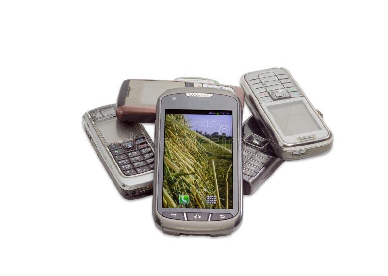Smartphone moderno en el fondo de teléfonos móviles viejos imagenes de archivo
