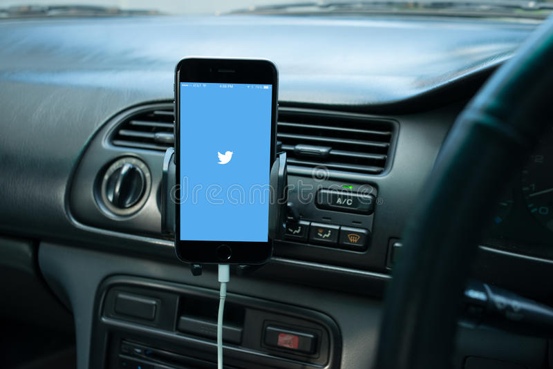 Smartphone mounted on a generic car's dashboard. With social media on its screen