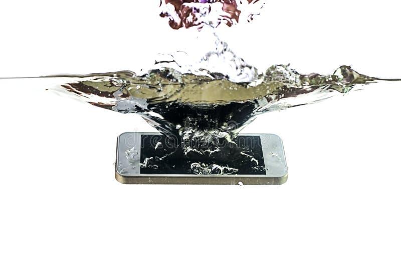 Smartphone na água e no respingo em um fundo branco imagens de stock