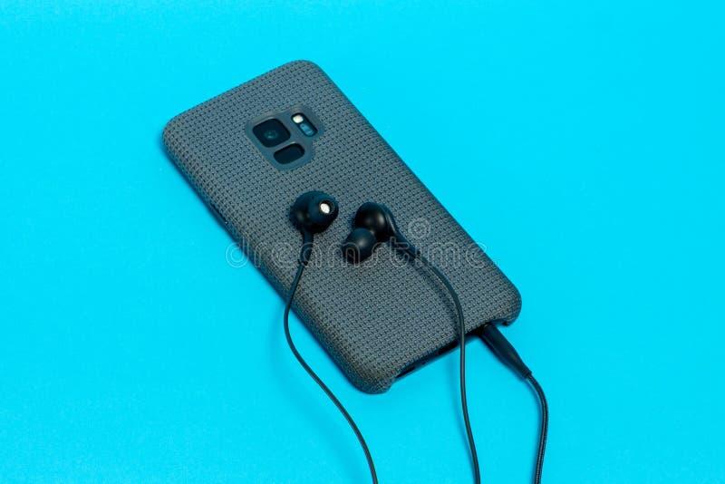 Smartphone na caixa à moda de matéria têxtil com os fones de ouvido conectados no fundo azul fotografia de stock
