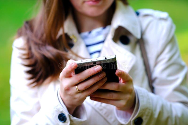 Smartphone nas mãos: conversa imagem de stock