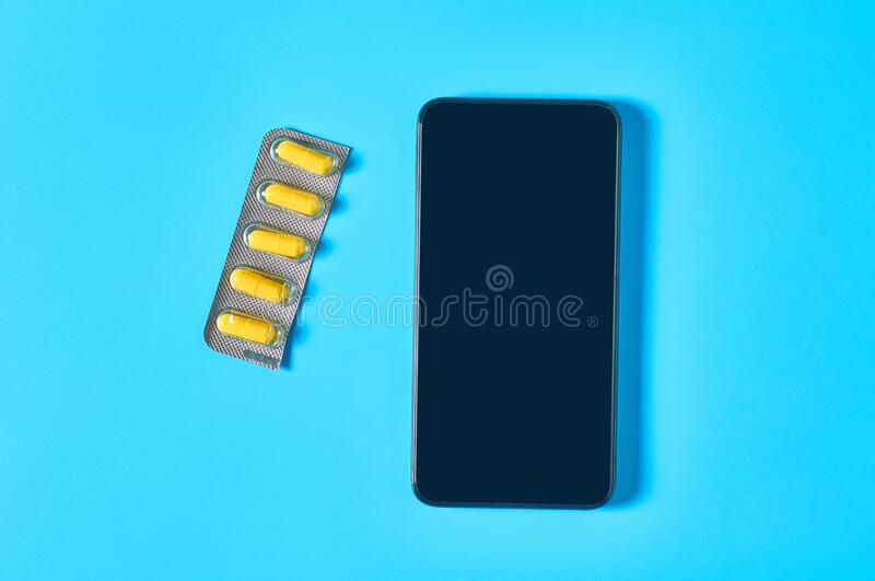 Smartphone near yellow capsules, pills on blue background. E-health, e-medicine concept. Online purchasing, consultation, medical assistance stock image