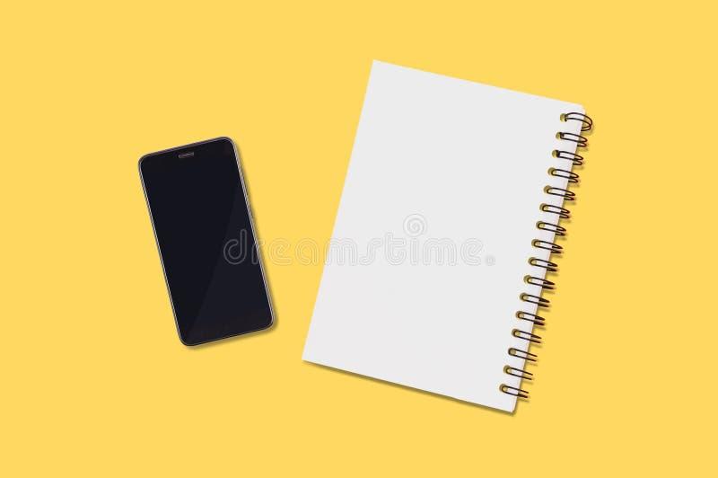 Smartphone negro y libreta de papel en blanco con mentiras espirales del tenedor en la tabla amarilla en oficina u hogar Visión s fotografía de archivo