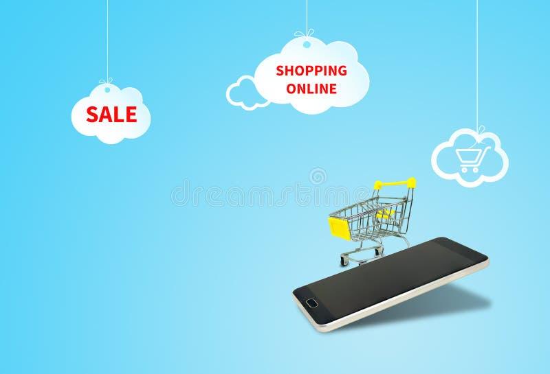 Smartphone nero e carrello giallo con le nuvole bianche su fondo blu illustrazione di stock