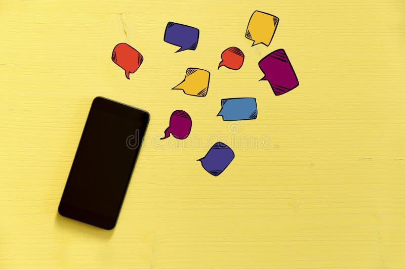 Smartphone no fundo amarelo com texto borbulha ao redor Messag imagens de stock royalty free