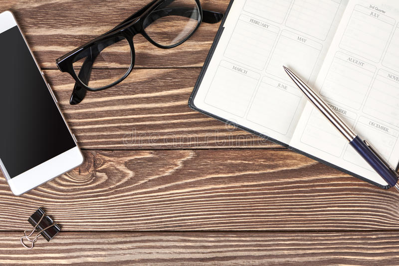 Smartphone, notebook and glasses on wooden background royalty free stock photos
