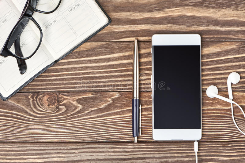 Smartphone, notebook and headphones on wooden background stock photos