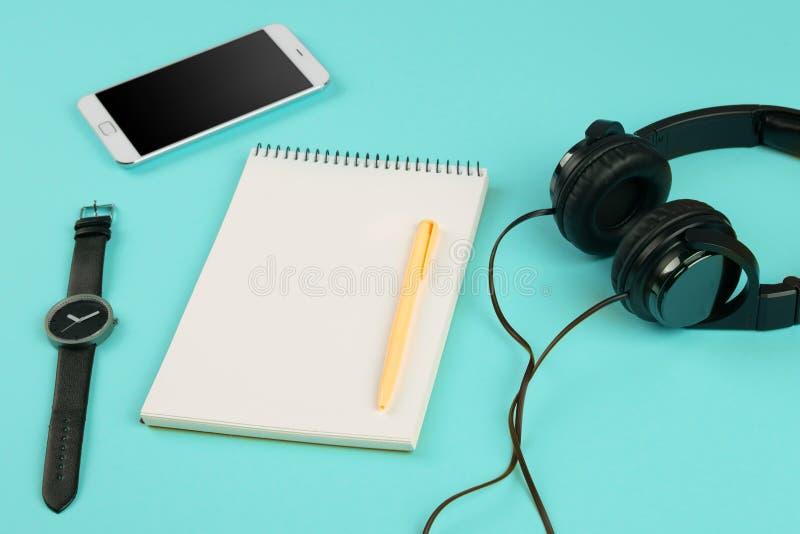 Smartphone, notepad, hörlurar, penna och klocka på färgen tillbaka royaltyfri bild