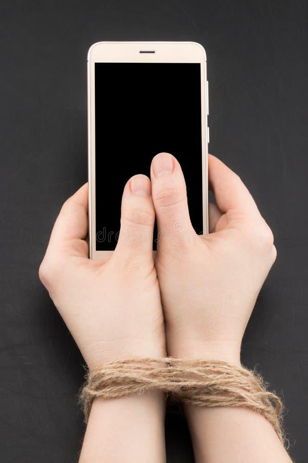 Smartphone o apego de Internet con las manos de la mujer atadas por la guita fotos de archivo